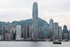 Colorful Star Ferry crossing Victoria Harbour in front of the Hong Kong Skyline stock photo