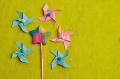 A colorful star shape lollipop with colorful pinwheels on a yellow background. A colorful star shape lollipop displayed with colorful pinwheels on a yellow Royalty Free Stock Photo