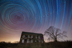 Colorful Star Trails above and Abandoned House Stock Image