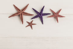 Colorful starfishes on wooden surface Royalty Free Stock Photos