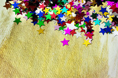 Colorful stars on gold background. Colourful, glittering stars on gold background. Christmas wishes or birthday message. Plenty of copy space Stock Images