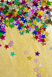Colorful stars on gold background, portrait. Colourful, glittering stars on gold background. Christams wishes or birthday message. Plenty of copy space, portrait Stock Photo