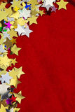 Colorful stars on red velvet background Stock Images