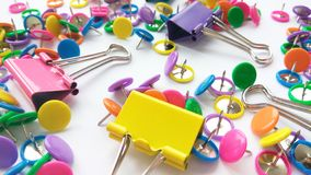 Colorful stationary, back to school, office, business and education concept. School and office supplies paper clips, pins on white. Background. Close up stock image