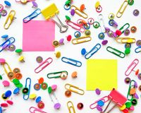 School and office supplies paper clips, pins, yellow notes, stickers on white background. Colorful stationary, back to school, office, business and education royalty free stock photos