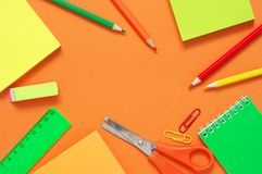 Colorful stationery set on orange. Colorful stationery set as frame on textured orange paper as  background. Top view, flat lay stock photos
