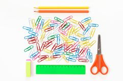 Colorful stationery set on white. Colorful paper clips and stationery items on white background. Top view, flat lay stock photos