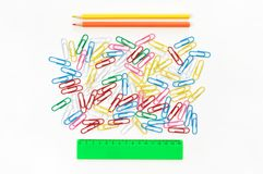 Colorful stationery set on white. Colorful paper clips, rule and pencils on white background. Top view, flat lay royalty free stock photo