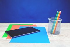 Colorful stationery and tablet on wooden desk royalty free stock image