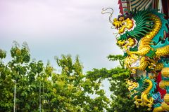 Colorful statue of Chinese dragon wrapped around the pillar. Beautiful statue of dragon carved around temple pole in Chinese stock photo