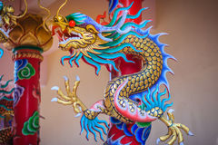 Colorful statue of Chinese dragon wrapped around red pillar. Beautiful statue of dragon carved around temple pole in Chinese royalty free stock photo
