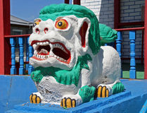 Colorful statue of shishi lion guards entrance to lamaist temple Royalty Free Stock Photo