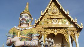 Colorful statues near Asian temple. Two bright multicolored statues located near ornamental Buddhist temple on sunny day. In oriental country. Mythical giant stock video footage