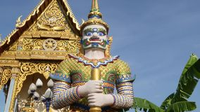 Colorful statues near Asian temple. Two bright multicolored statues located near ornamental Buddhist temple on sunny day. In oriental country. Mythical giant stock video