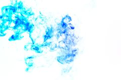 Colorful steam exhaled from the vape with a smooth transition of color molecules from turquoise to blue on a white background like stock images