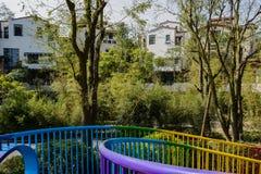 Colorful steel banisters of footbridge before houses in woods at. Colorful steel banisters of a footbridge before houses in woods at sunny winter noon,Chengdu Royalty Free Stock Photo