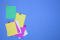 Colorful stick note papers on blue background. Stock Photos