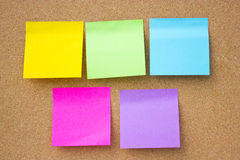 Colorful sticky notes. Wooden board with five blank colorful sticky notes Royalty Free Stock Photo