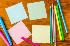 Colorful sticky notes and writing utensils on wooden desk stock image