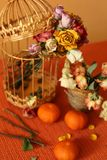 Riot of orange. A colorful still-life made up of dry small roses, golden cages, marndarins Stock Photo