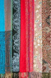 Colorful stoles with ethnic ornament. Colorful variety of palantines with ethnic ornament hanging for sale royalty free stock images