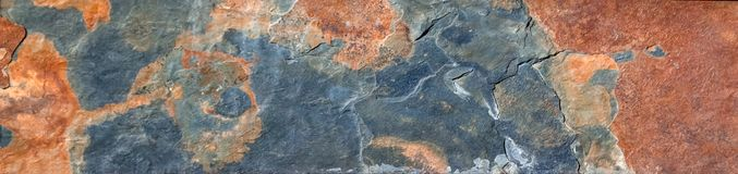Colorful stone slab texture abstract background. Blue orange and rust colored textured abstract stone slab background closeup royalty free stock photo