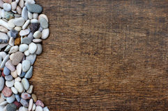 Colorful stones on background wood texture. Pile of colorful stones with waveform on background wood texture Royalty Free Stock Image