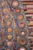 Colorful stones and ceramic created on red brick. Royalty Free Stock Images