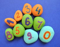 Colorful stones with painted ratings. Colorful stones with painted numbers on blue background royalty free stock image