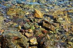 Colorful stones rocks trasparent sea water, landscape Stock Photos
