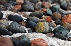 Colorful rocks and some snow in between. Colorful stones with some red, orange, yellow, green, blue and black tones. There is also snow in between them Royalty Free Stock Photo