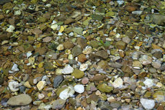 Colorful  stones in the water. Royalty Free Stock Photography