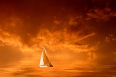 Colorful stormy sunset. Solitary sailboat on the sea in a cloudy orange sunset Stock Images