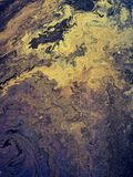 Colorful Strange artistic pattern caused by oil or grease spilled on water. Abstract yellow slick or oil on top of water puddle  makes for beautiful artistic royalty free stock photography
