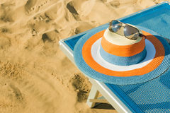Colorful straw hat with sunglasses on top, set on a beach chair in the sand Royalty Free Stock Photos