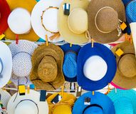Straw summer hats on market stall outdoor. Colorful straw hats hanging on the market stall outdoor. Bright summer woman hats for sale royalty free stock image
