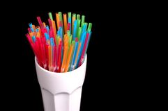 Colorful straws in white glass. Vibrant colored straws in white glass Stock Photos