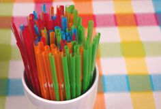 Colorful straws in white glass on checkered mat. Vibrant colored straws in white glass on colorful mat Royalty Free Stock Photos