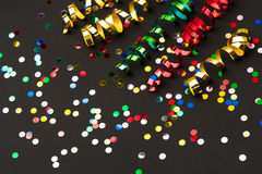 Colorful streamer, confetti, black background Royalty Free Stock Photos