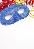 Colorful streamers and blue glittering mask on white table close up Stock Photos