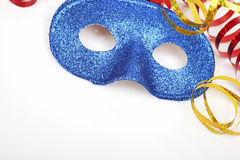 Colorful streamers and blue glittering mask on white table close up Stock Photo