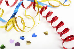 Colorful streamers and confetti on white table close up Stock Photos
