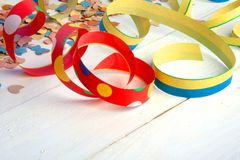 Colorful streamers and confetti on white wood. Colorful streamers and confetti on a white wooden table for a carnival party royalty free stock image