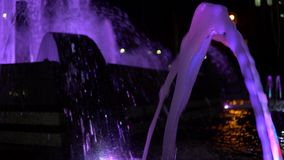 Colorful streams of water in fountain at night time, super slow motion. Colorful fountain with bright illumination against the black sky background at the stock video footage