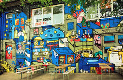 Colorful street art by unknown artist on wall of popular outdoor cafe of Berlin Stock Photo