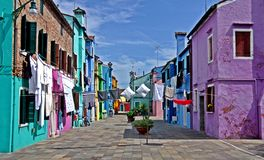 Colorful street of Burano. The beautiful colorful small houses of the isle of Burano, Venice, on a sunny spring day. Linen and sheets are hanged outside to dry Royalty Free Stock Image