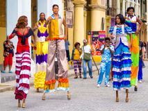 Colorful street dancers on stilts in Old Havana. HAVANA,CUBA- JANUARY 24,2015 : Colorful band of street dancers on stilts and musicians on a beautiful Old Havana Stock Photography