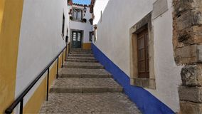 A colorful Street in the medieval town of Obidos, Portugal. Obidos is a city with history and culture. It combines the middle ages and the present one. Photos Stock Image