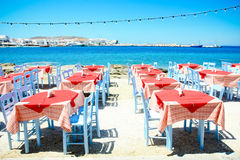Colorful street restaurant by the sea. Bright colors of the table and chairs next to the blue waters of the adriatic Stock Images