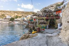 Matala street. Colorful street with  restaurants and taverns in Matala village , Crete , Greece , Europe . At sunset time . View on the tavern and beach Stock Images